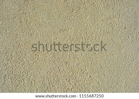 Yellow bright background, construction wall with very small glass stones matte white and gray with a reflection of the sun #1155687250