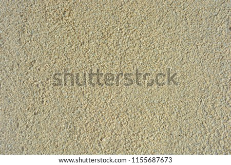 Yellow bright background, construction wall with very small glass stones matte white and gray with a reflection of the sun #1155687673