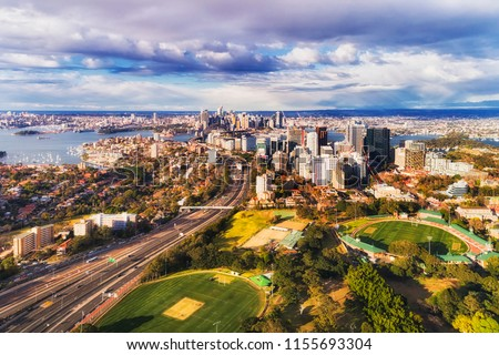 North Sydney oval with North Sydney high-rise towers along Warringah freeway and further down to SYdney harbour with city CBD in elevated aerial view. Royalty-Free Stock Photo #1155693304