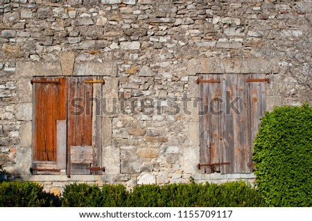 old brown wooden shutters in stone wall #1155709117