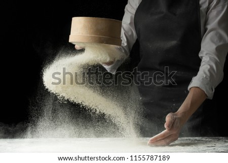 An experienced chef in a professional kitchen prepares the dough with flour to make Italian Italian pasta. concept of nature, Italy, food, diet and biology. on a dark background #1155787189