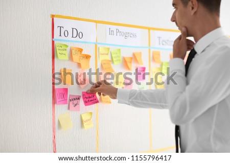 Man with sticker near scrum task board in office #1155796417