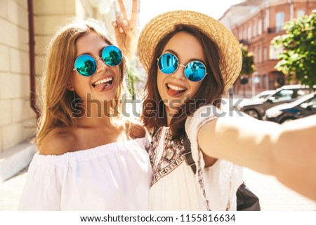 Two young female stylish hippie brunette and blond women models in summer sunny day in white hipster clothes taking selfie photos for social media on smartphone on the street background.Showing tongue