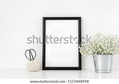Black frame mockup in interior with vintage elements. Frame mock-Up poster or photo frame and supplies on table near white wall. Desk space, copy space. Background. Template #1155848998
