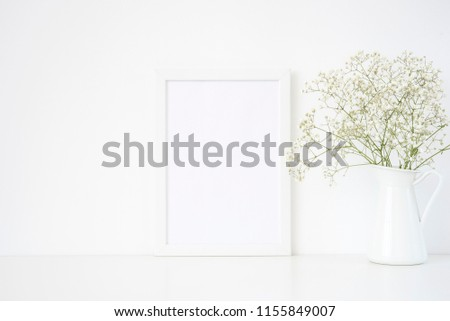 White frame mockup A4 in interior. Frame mock up background for poster or photo frame for bloggers, lettering, art and design. Indoor, frame on table with delicate flowers in jug.. Summer sea mood #1155849007
