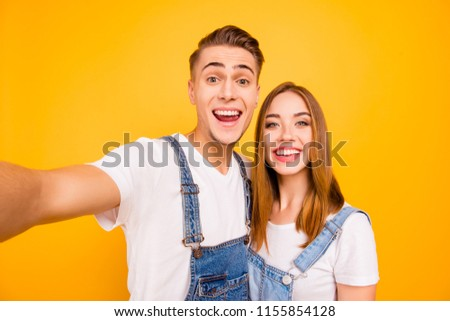 Self portrait of funny foolish cheerful adorable young cute couple smiling showing teeth, looking straight with opened mouths over yellow background, isolated #1155854128