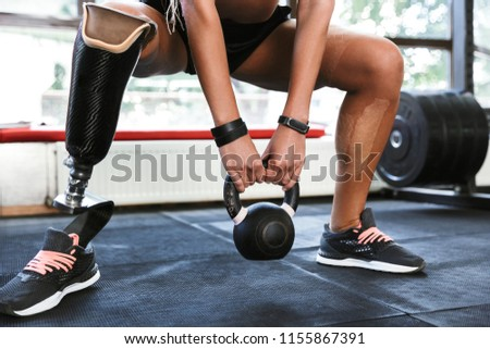 Cropped image of amazing strong disabled sports woman make sport exercises with equipment in gym. #1155867391