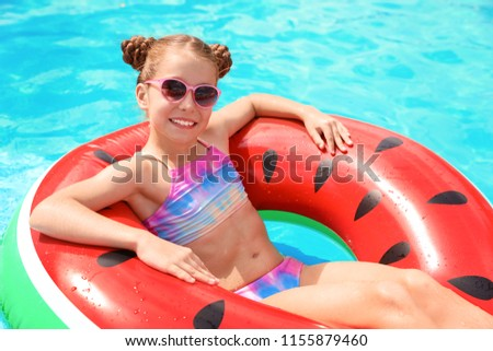 Little girl with inflatable ring in swimming pool #1155879460