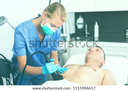 Female doctor is doing vacuum massage procedure for anti-fat to patient in estetic clinic. #1155904657