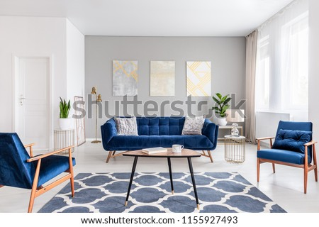Real photo of a modern living room interior with a sofa, armchairs, table, paintings and patterned carpet #1155927493