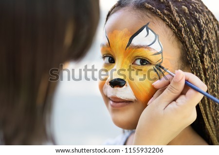 Children face painting. Artist painting little african-american girl like tiger, copy space #1155932206