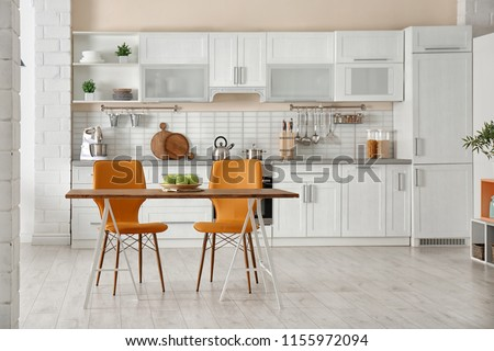Stylish kitchen interior with dining table and chairs #1155972094