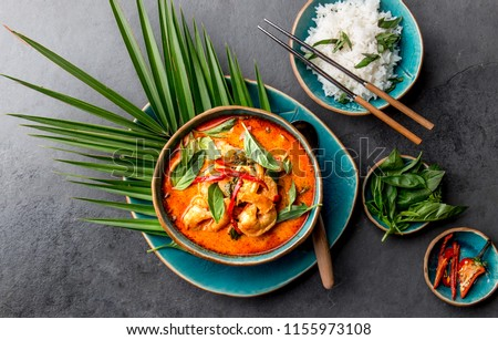 THAI SHRIMPS RED CURRY. Thailand tradition red curry soup with shrimps prawns and coconut milk. Panaeng Curry in blue plate on gray background. #1155973108