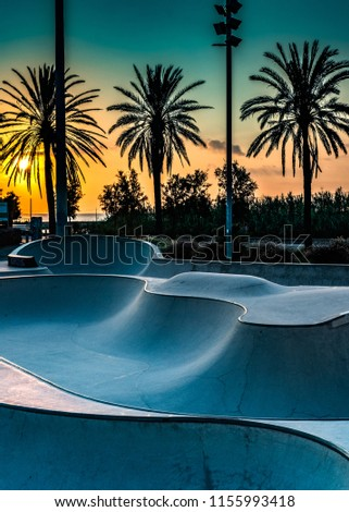 Barcelona, Spain: Concrete skatepark with tubes and jumps at sunset  #1155993418