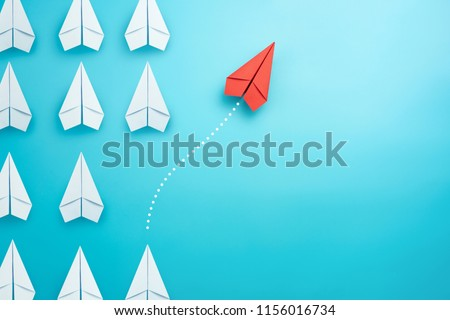 Group of white paper plane in one direction and one red paper plane pointing in different way on blue background. Business for innovative solution concept. #1156016734