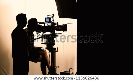 Video production behind the scenes which film crew team in silhouette shooting or recording tv movie commercial with professional equipment such as high definition 4k camera with monitor studio set.