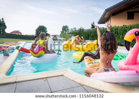 Multiracial group of friends having party in a private villa with swimming pool - Happy young people chilling with shaped air mattresses #1156048132