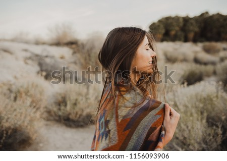Smiling, beautiful hipster traveler girl in gypsy look and windy hair, in desert nature.  Artistic photo of young hipster traveler girl in gypsy look, in Coachella Valley in a desert valley in Souther #1156093906