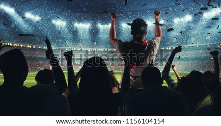 Fans celebrating the success of their favorite sports team on the stands of the professional stadium while it's snowing. Stadium is made in 3D. #1156104154