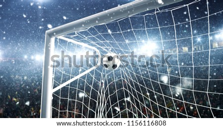 Photo of the ball that flies into a goal on a professional soccer stadium while it's snowing. Stadium and crowd are made in 3D.