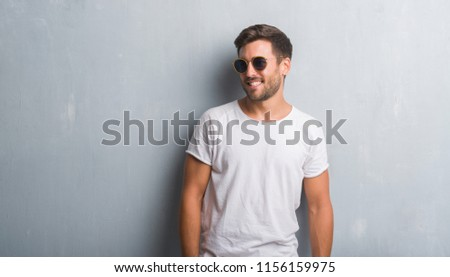 Handsome young man over grey grunge wall wearing sunglasses looking away to side with smile on face, natural expression. Laughing confident. #1156159975