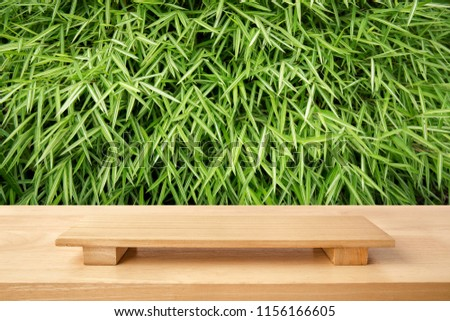 Empty sushi board on wood table with bamboo green leaves background. Top view of plank wood for graphic stand, interior design or montage display your food product of culture China and japan.