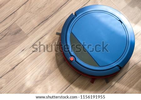 Blue robotic vacuum cleaner on laminate wood floor #1156191955