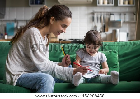 Smiling baby sitter and preschool kid girl drawing with colored pencils sitting on sofa together, single mother and child daughter playing having fun, creative family activities at home concept #1156208458