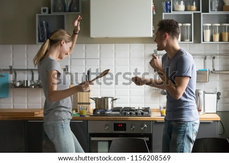 Funny young couple dancing to music together enjoying cooking in the kitchen, man and woman in love having fun preparing breakfast food feeling happy and carefree on weekend lifestyle at home #1156208569