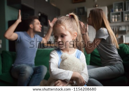 Kid daughter feels upset while parents fighting at background, sad little girl frustrated with psychological problem caused by mom and dad arguing, family conflicts or divorce impact on child concept Royalty-Free Stock Photo #1156208680