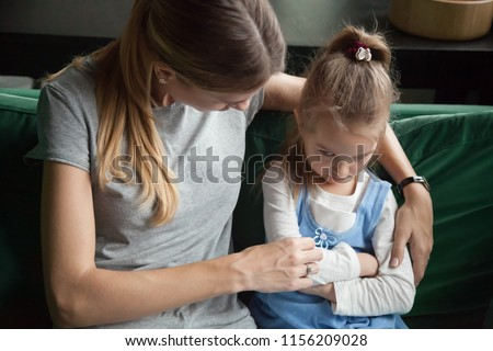 Sulky angry offended aggrieved child girl pouting ignoring avoiding mother trying to embrace and talk to upset stubborn daughter about misunderstanding problem, difficult kid insult behavior concept #1156209028