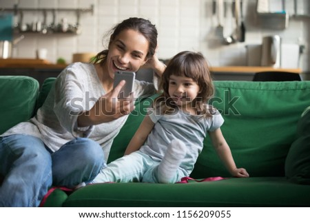 Happy mother laughing taking selfie with child daughter on smartphone at home, smiling single mom and cute girl playing making photo posing for self portrait, mommy and kid shooting stories