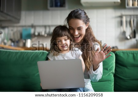 Happy mother and kid daughter waving hands looking at web camera using laptop for video call, smiling mom and child girl having fun greeting online by computer webcam making videocall via application Royalty-Free Stock Photo #1156209058