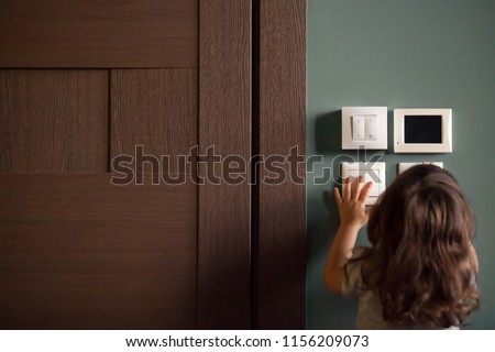 Rear view at little careless child girl exploring house playing turning light switches, home electricity danger security, electric shock risk and kids safety, energy power saving concept, copy space #1156209073