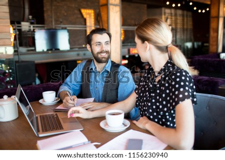Trendy woman and man sitting with laptop and teacups at table chatting and working in relaxation  #1156230940