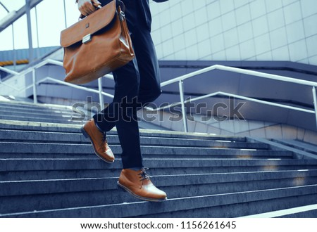 Businessman with bag in his hand walking down steps. Cropped shot of elegant man in suit taking step down on stairs. #1156261645