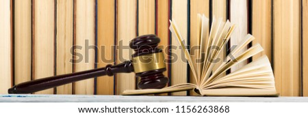 Legal Law concept - Open law book with a wooden judges gavel on table in a courtroom or law enforcement office. Copy space for text #1156263868