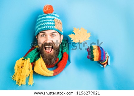 Happy bearded man with autumnal maple yellow leaf in hand. Bearded man in colorful hat look through paper and hold autumn leaf. Autumn mood. Autumn time. Isolated. Through paper. Emotions.