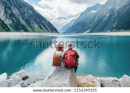 Travelers couple look at the mountain lake. Travel and active life concept with team. Adventure and travel in the mountains region in the Austria #1156349101