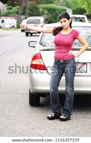 SEATTLE, WA. NOV 10, 2006. CIRCA: Sexy female beauty standing in the rain next to her car with a dead battery trying to thumb a ride home. #1156397239