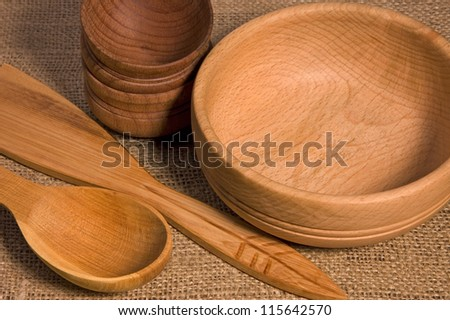 Wooden bowls and spoons on burlap close-up #115642570