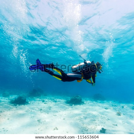 Silhouette of Young Man Scuba Diver between Water Surface and Sea Bottom Royalty-Free Stock Photo #115653604