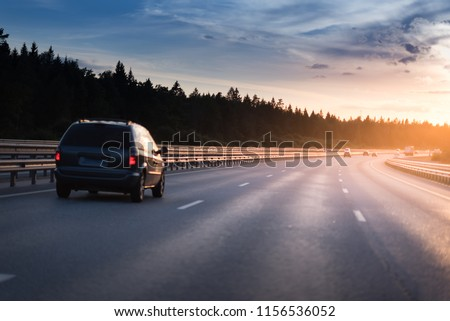 Highway traffic in sunset. minivan on the asphalt road with metal safety barrier or rail. Pine forest on the background #1156536052