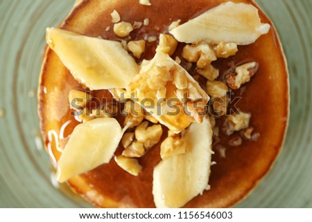 Tasty pancakes with sliced banana and walnuts on plate, closeup #1156546003