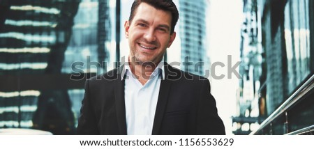 Portrait of an handsome businessman in an urban setting. Cheerful man in the street #1156553629