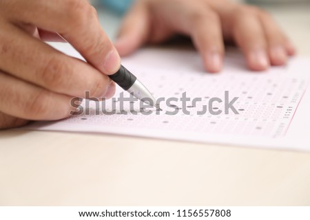 Picture of man is filling OMR sheet with pen. #1156557808