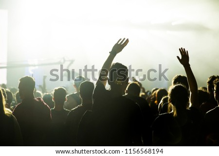 Crowd at concert. Stage lights and hands in the air. People enjoying the party. #1156568194