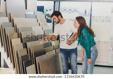 Couple looking ceramic and tiles for their new home floor. They are choosing in furnitures store Royalty-Free Stock Photo #1156620670