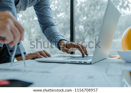 Concept architects, equipment architects ,Working On laptop with a blueprint and Model in the office Selective Focus #1156708957