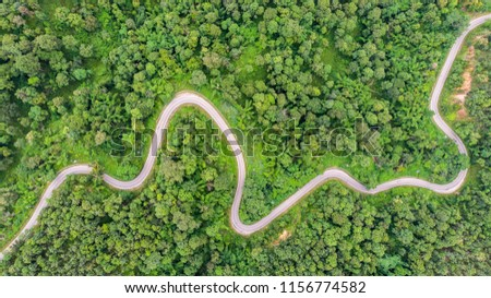 Aerial view of countryside road passing through the green forrest and mountain #1156774582